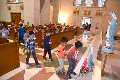 St. Cyril students put flowers at the base of a statue of Mary during their May Crowning on Tuesday.