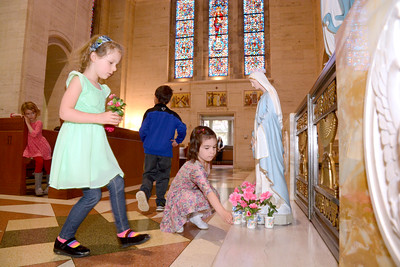 St. Cyril Pre-K students Rosie Morris, left, and Isabel Helwig, places flowers at the base of a statue of Mary during their May Crowning on Tuesday morning.