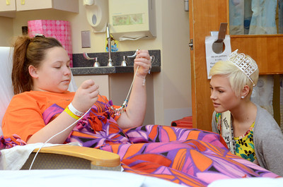 Janet Weis Children's Hospital patient Samantha Darrup, 12, left, Kulpmont, shows Miss Teen USA Sydney Robertson, 16, Williamsport, her charm necklace she has started since being in the hospital.