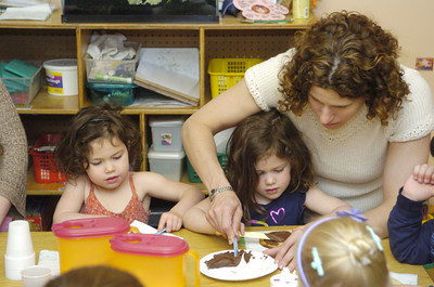 Celo, 3, left, and Olivia Hummel, 3, get help from their mother Rona Hummel, decorating their cookies during Thursday's mommy and me day at Lutz Day Care in Danville.