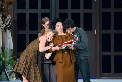 Danville High School actors Madison Kovach, left, Emma Sharpe, and Matt Riegel, right surround and hug Bethan Fegley during their rehearsal for the play, Moose Murders, on Monday night.