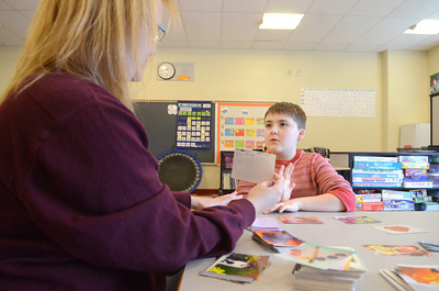 Paraprofessional Barb Simons works with Liberty Valley student John Manning, 10, in his classroom on Wednesday with a matching game.