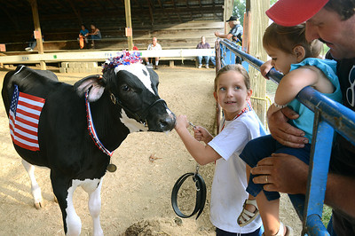 Courtney Shuman, 8, of Bloomsburg shows brings her calf, Nevaeh, to meet Analee McCanney, 19 months, and Dean Woodruff during the Pet and Toy Parade Wednesday Aug 15, 2012 at the Montour-Delong Fair.