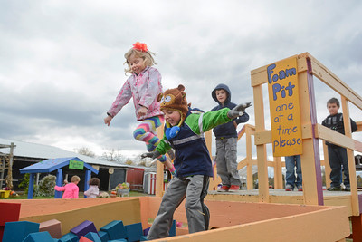 Kindergarten students Alaina McDonough, left, and Nathan Klein, jump into the foam pit at Pumpkinville in Riverside on Thursday morning as they and fellow Danville Primary School classmates were rewarded for doing well in a school fundraiser.
