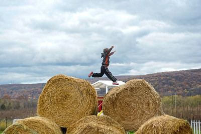 Danville kindergarten student Braxton Girardi jumps across giant hay bales at Pumpkinville in Riverside as he and fellow classmates got a reward for doing well in a school fundraiser.
