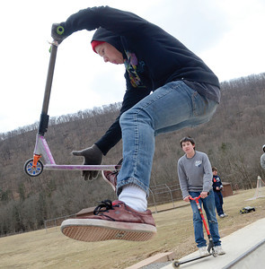 Austin Young, 18 Danville, lands a trick on his scooter at the Hess Recreation Area on Sunday; Jared Huntington, 15 Danville watches in the background.