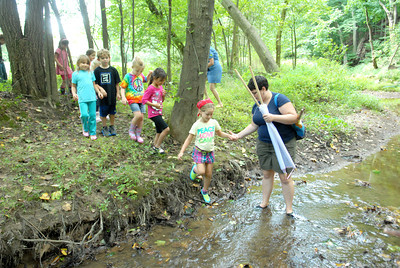 Bloomsburg University senior Hannah Davis, right, helps St.Cryil kindergarten studentThea Sommer, 5, and her classmates, across a creek for a environmental lesson on Friday.