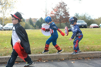 St. Cyril students Captain America, Jake Helwig, 4, left, and Captain America, Junter Auton, 4, right, walk long in their school's Halloween parade on Friday morning in Danville.