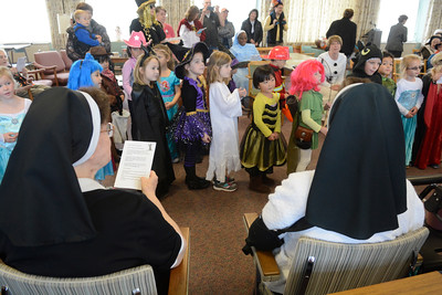 Sisters Irene Rose Kmetz, left, and Rosanne Kmetz, right, watch students from St. Cyrils in Danville sing for them on Friday while dressed in their Halloween costumes.