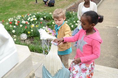 St. Cyril students Quintin Bergey, 4, left, and Sophia Yohannes, 6, put a crown of flowers on a statue of Mary, Jesus's mother, at St. Cyril's on Friday for their May crowning event.