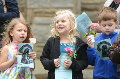 St. Cyril students Pia Rock, 5, left, and Hadley Starankovic, 5, wait their turn to place flowers at the base of a statue of Mary, the mother of Jesus, during St. Cryil's May crowning event.