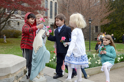 St. Cyril students Irfan Ahmed, 5, left, John Friedenberg, Greta Facktor, 4, and Sarah Packard, 5, all place flowers at a statue of Mary, the mother of Jesus, on Friday during their May crowning event.