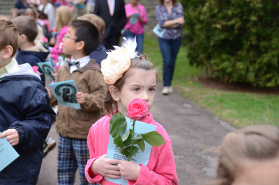 Bryleigh Gill, 5, carries a flower to place at the feet of a statue of Mary, the mother of Jesus, at St. Cyril's on Friday for their May crowning event.