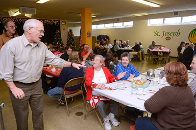 Joe Ward, left, talks with Nancy Hodge and Carol Reibsome while serving them part of their meal at St. Joe's in Danville annual Thanksgiving dinner on Thursday.