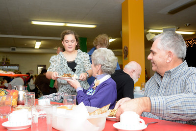 Laura Hilkert passes food to Pat and Nick Burlone of Riverside at the St. Joe's annual Thanksgiving dinner on Thursday afternoon.