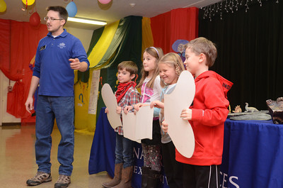 Mike Kaczmarczik of the Academy of Natural Sciences, left, does a demonstration about fossils with St. Joseph of Danville students Luke Hilkert, 8, Maia Jacks, 8, Avery Geffken, 7, and Merik Brayford, 7, during a program on dinosaurs on Tuesday.
