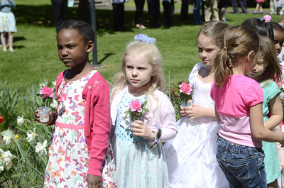 St. Cyril students Sydney Clarke, 5, left, and Hadley Starankovic, 4, wait to place their flowers during a May Crowning ceremony on Thursday at St. Cyril's in Danville.
