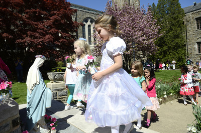St. Cyril students Hadley Starankovic, 4, left, and Thae Sommer, 5, place flowers at the foot of a statue of the Virgin Mary during a May Crowning ceremony on Thursday at St. Cyril's in Danville.