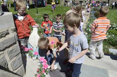 St. Cyril students in Danville place flowers at the feet of a statue of the Virgin Mary on Thursday during a May Crowning ceremony.