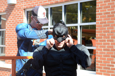 Adam Thomas, dressed as Superman, helps Eric Ruhl into his Batman costume before they start washing windows at the Geisinger-Bloomsburg Hospital on Tuesday.