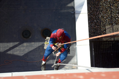 Josh Williams dressed as Spiderman, lowers himself down to where he was washing windows Tuesday afternoon at the Geisinger-Bloomsburg Hospital.