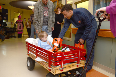 Clayton Spencer, 2, left, New Albany, gets a treat from Bucknell mens basketball player John Azzinaro during a Trick-or-Treat event on Thursday at the Janet Weis Children's Hospital in Danville.