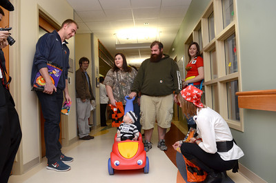 Geisinger pediatric patient Judson Shepher, 1, Towanda, looks up at six foot nine inch Bucknell mens basketball player Ben Oberfeld, left, as he was pushed around by Raga Chacona and Brandon Shepherd at a Trick-or-Treat event Thursday afternoon at the Janet Weis Children's Hospital in Danville.