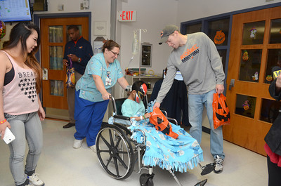 Chelsea Seo, left, Mt. Pocono, looks on as her son Christian Simms, 6, gets a treat from Bucknell mens basketball player Ben Brackney during a Trick-or-Treat event for patients at the Janet Weis Children's Hospital in Danville on Thursday.