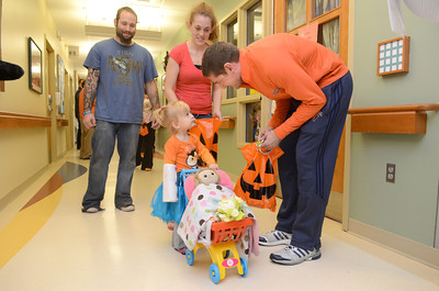 Kaylnn Spotts, 2, Lock Haven, gets a treat from Bucknell mens basketball assistant coach Dane Fischer on Thursday at the Janet Weis Children's Hospital in Danville during a Trick-or-Treat event for patients.