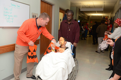 Bucknell men's head basketball coach Dave Paulsen passes out a treat to Deyvaun Williams, Williamsport, on Thursday who was being pushed by his father Kenneth, during a Trick-or-Treat event at the Janet Weis Children's Hospital in Danville.