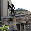 Behind this statue is the Bank of Montreal's main Montreal branch at Place d'Armes  in Old Montreal.