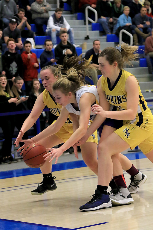 . Montachusett Regional Vocational Technical School\'s Ashley Girouard goes after a loose ball with two Hopkins Academy players during the MIAA Basketball State Semi-Finals at Worcester State University on Wednesday night. SENTINEL & ENTERPRISE/JOHN LOVE