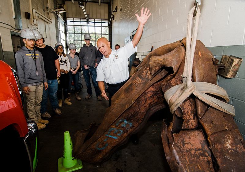 Lt. Richard Liberatore shows off a piece of steel from the Twin Towers at the Fitchburg Fire Department on Wednesday, October 4, 2017. Monty Tech masonry students were on hand to install bricks around the base of the 9/11 monument. SENTINEL & ENTERPRISE / Ashley Green