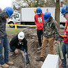 Montachusett Regional Vocational Technical School electrical students where digging a trench in front of the Fitchburg firefighters monument on the Upper Common to put in accent lighting for the monument. It should be done in time for Firefighter Sunday which is the second Sunday in June where many cities and towns in the Commonwealth honor firefighters. The little bit of rain didn't stop them as they worked hard to get it done. Instructor Dean Lepkowski, in white helmet, works with some of the seniors. SENTINEL & ENTERPRISE/JOHN LOVE