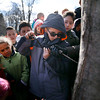 HOLLY PELCZYNSKI - BENNINGTON BANNER Classmates watch intently as 5th grader Jason Vickers uses a hand drill to tap a sugar maple tree at Monument Elementary school on Friday morning in Bennington. Fourth and fifth graders at monument have been studying Vermont and will collect all the sap and boil it to make maple syrup in the spring.