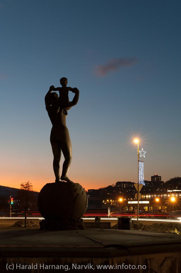 Statue Narvik torg, dame med barn på armen, Narvik sentrum, torg, mørketidsbilde 20. desember 2012 kl 1500.