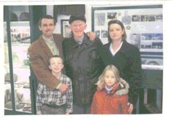 """St. Hubert, Belgium (Pic 2 of 2.)<br /> <br /> Olivier Gillard with his wife Nadine and children.<br /> Olivier Gillard is a young man who lives in St. Hubert, Belgium where the 87th Infantry Division fought. <br /> <br /> He is the creator of this little Museum in his home, <br /> and has a collection of 87th Infantry Division memorabilia, <br /> photos, stories, weapons, artifacts, diaramas, etc.<br /> They were furnished by the men of the 87th Infantry Division.<br /> <br /> You can see the Displays of Tribute to the 87th Infantry Division soldiers in the background.<br /> <br /> Many 87th Division members and wives visited the museum, Called the<br /> """"87th Division Exposition"""" while on the VBOB Tour Dec 2004....<br /> (60th anniversary).<br /> There are many legends of the soldiers  throughout the museum..<br /> with their personal stories.<br /> <br /> This is a fine little Musuem to the 87th Infantry Division which fought in the St. Hubert sector.<br /> <br /> See the outside of his basement museum in Pic 1 of 2."""