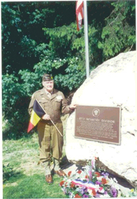 "John McAuliffe, M-347 in Army uniform at the plaque on the boulder at <br />              ""Bloody Crossroads"" <br />               Pirompré, Belgium.<br /> <br /> Plaque dedication June 1996.<br /> <br /> Here are kind words sent to the gallery comment section by Mr. Gilbert Stevenot:<br /> <br /> John McAuliffe is a dear friend, who remain the ambassador-at-large, to honor the acts of bravery of the 87th Infantry Division, during the bitter campaign in the Battle of the Bulge.<br /> <br /> I was the main coordinator of the officers' club Corlux to erect a momument in Pirompré and plaques in Tillet, Bonnerue, Moicy and St-Hubert, <br /> where the men of the division have fought bloody fights to put out of action the tenacious German Army, through the hilly and dense forests of the Ardennes, on their way to liberate the besieged Nuts City. <br /> <br /> All those monuments in the Ardennes, in Quincy or elswhere in the States, represent a great link to the past and to those who serve today in the world to bring peace to oppressed people.<br /> <br /> As a former interpreter at the 12th Army Group, <br /> I am proud of what I have done during the war and since the end of it, <br /> and the pleasure to meet again the friends of the past. <br /> <br /> I will never forget what they have done to liberate my country.<br /> <br /> God bless America.<br /> Steve"
