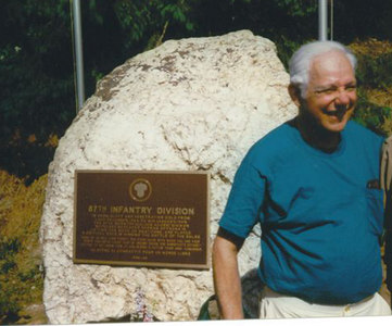 "Mitch Kaidy, D-345 at the plaque on the boulder at <br /> ""Bloody Crossroads"" <br /> Pirompré, Belgium.<br /> <br /> Plaque dedication June 1996.<br /> <br /> As Monuments Committee chairman,<br /> Mitchell Kaidy; D-345, suggested the plaques,<br /> wrote all the texts for them,<br /> (some translated into French by Gilbert Stevenot of Rochefort),<br /> wrote nearly all the speeches, including those in French,<br /> (they were translated from English)<br /> and presided at the ceremonies in four villages. <br /> <br /> Mr. Kaidy had the plaques made in Cincinnati and shipped as antiques (to avoid duty) to Gilbert Stevenot."