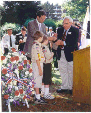 Left:<br /> Benjamin Patton, the Grandson of <br /> Gen. George S. Patton III; WW-II !!<br /> He was a main speaker at the Dedication.<br /> <br /> Right:<br /> Also shown is Stanley A. Wojtusik, <br /> National President of the <br /> Veterans of the Battle of the Bulge.<br /> (VBOB)<br /> <br /> The two young scouts are the sons of the Veteran who furnished the Color Guard from the Massachusetts National Guard 1st Artillery, <br /> 102D Field Artillery, Quincy, MA.