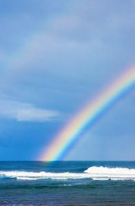Rainbow falls into the ocean off Sunset Point North Shore of O'ahu, Hawai'i