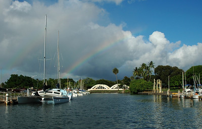 A rainbow appears over Anahulu Stream Bridge, or Rainbow Bridge,  a Hale'iwa landmark near the Hale'iwa Small Boat Harbor  North Shore, O'ahu, Hawai'i