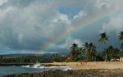 Rainbow over Ali'i Beach lifeguard station  and surfers in Hale'iwa on the North Shore of O'ahu, Hawai'i