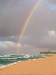 Through the dark clouds a rainbow appears  over the beautiful turquiose ocean on a stormy day  North Shore, Oahu, Hawaii