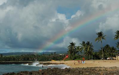 Rainbow over Ali'i Beach lifeguard station  and surfers in Hale'iwa on the North Shore of O'ahu, Hawai'i