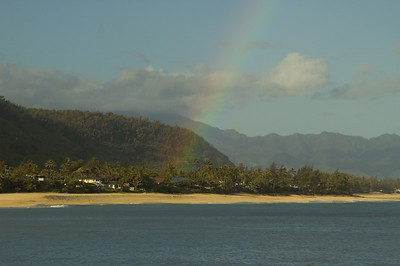 Against a soft blue sky with rainclouds,  a rainbow appears over Rocky Point  North Shore of O'ahu, Hawai'i    North Shore, Oahu, Hawai'i North Shore of O'ahu, Hawai'i
