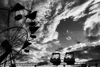 D37:Joyrides in a Siliguri amusement park look like a giant assembly line,framed against the dramatic monsoon sky