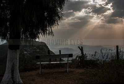 D14:The rays of sun break through the clouds,lighting up the empty bench in Selim Hill,Kurseong,West Bengal