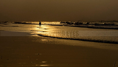 D20:A newly wed couple stand in the golden waters of the sea at dawn,in Tajpur,a small fishing village in West Bengal