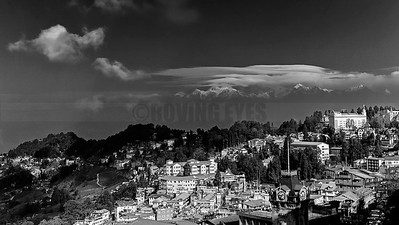 D21:Darjeeling town (West Bengal )basks in the sun with  Khangchendzonga peeking out from under the clouds in the background